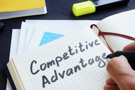 Man is writing words Competitive advantage in the notepad.