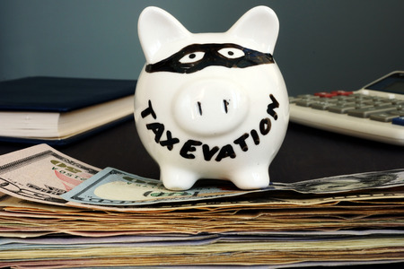 Tax evasion written on a piggy bank. Stock Photo