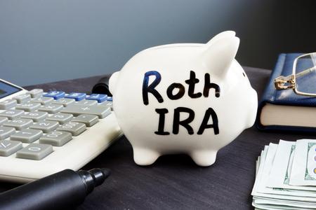 Roth IRA written on a piggy bank. Retirement plan.
