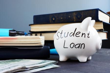 Préstamo para estudiantes escrito en una alcancía y dinero. Foto de archivo