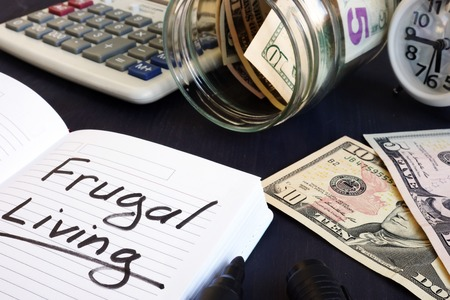 Frugal living written on a note pad and money.