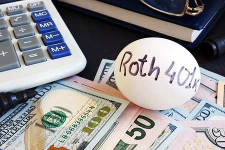Roth 401k written on a side of egg and money. Stock Photo
