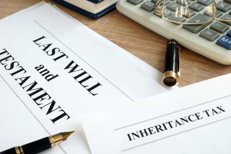 Inheritance tax and last will and testament on a desk.