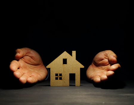 Hands offers model of house. Mortgage concept.