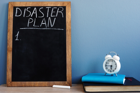 Disaster Plan written on a blackboard and notepads. Stock Photo