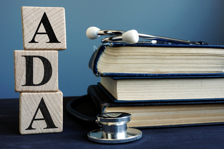 Word ADA Americans with Disabilities Act from cubes and books. Stock fotó