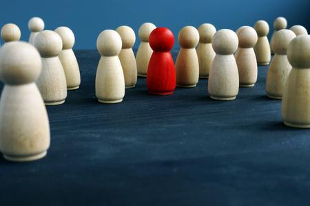 Figure in legno e una figura rossa. Essere diverso. Distinguersi dalla folla.