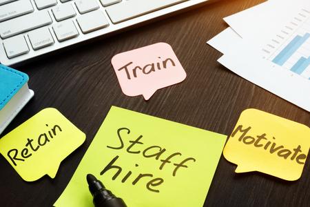 Staff hire, train, motivate and retain written on a memo sticks. Stock Photo