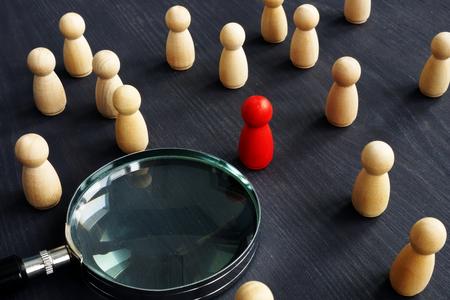 Holzfiguren und Lupe. Personalauswahlkonzept. Anstellen von Menschen, um zu arbeiten. Standard-Bild