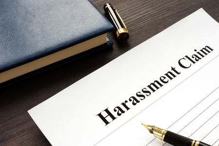 Harassment Claim and pen on a wooden desk. Stock Photo