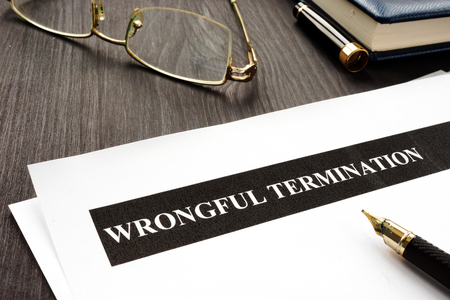 Documents about Wrongful termination on a wooden desk. Stock Photo