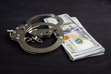 Menottes et argent. Des dollars pour les cautions.
