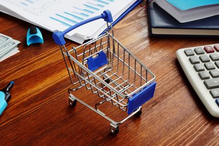 Handelsmarketing. Einkaufswagen auf einem Schreibtisch. Standard-Bild