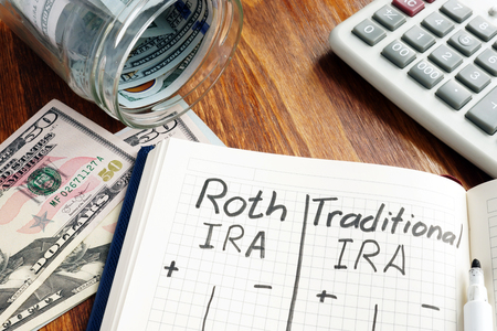 Roth IRA vs Traditional IRA written in the notepad. Stock Photo