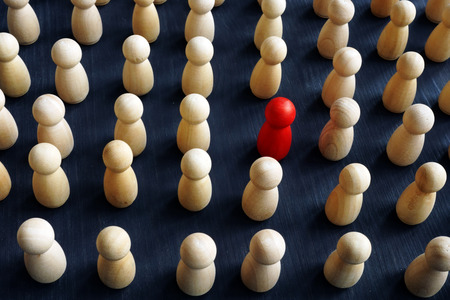 Unique, individual and think differently. Crowd of wooden figures and red one.