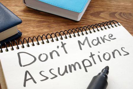 Don't Make Assumptions. Notepad with marker on a table.