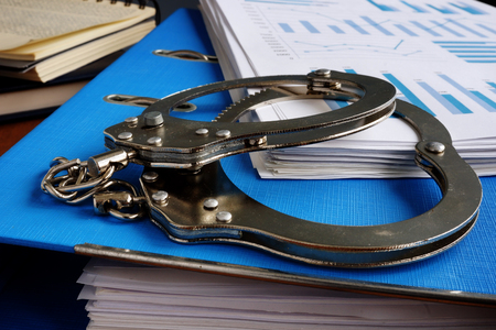 Tax evasion. Handcuffs and pile of financial papers. Stockfoto - 116482532