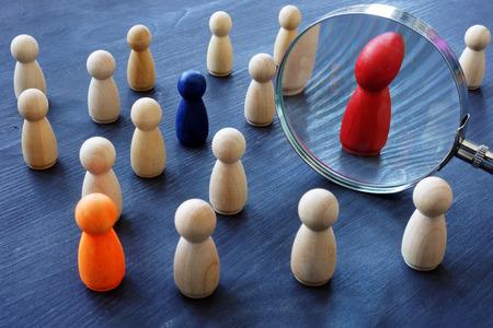 Concept de recherche de talents. Loupe et figurines en bois.