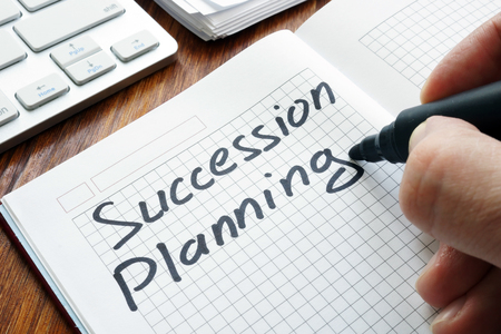 Man is writing succession planning in the book. 스톡 콘텐츠