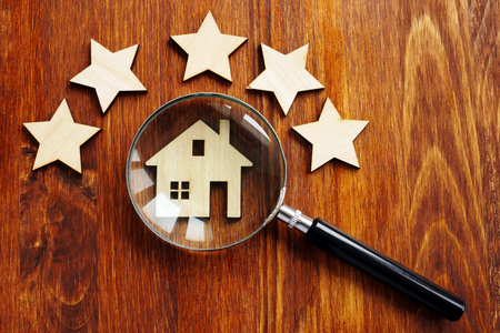 Home appraisal. House with magnifying glass and five star.