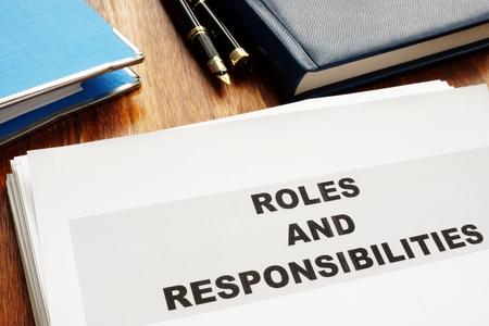 Rollen- und Verantwortungsdokumente auf einem Schreibtisch. Standard-Bild