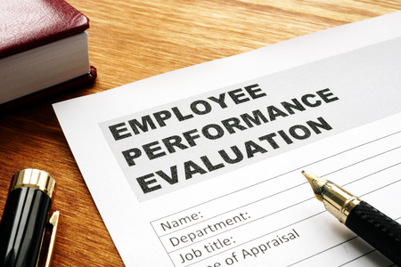 Employee performance evaluation form on a desk. Stok Fotoğraf