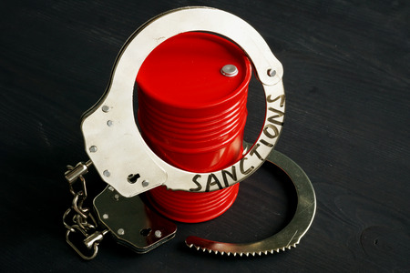 Trade embargo and sanctions concept. Barrel of oil and handcuffs.