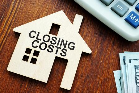 Abschlusskosten. Modell von Haus und Geld.