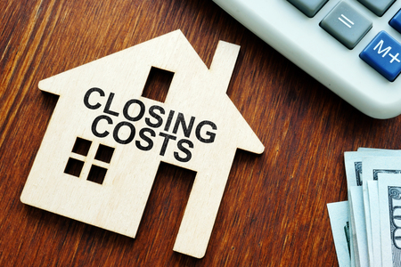 Closing costs. Model of house and money. 免版税图像