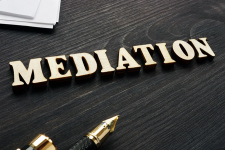 Mediation from wooden letters and agreement documents.