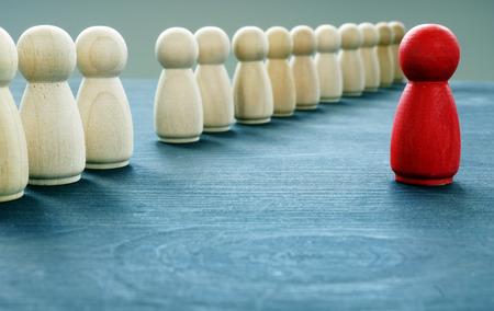 Seien Sie einzigartig und anders. Rote Figur hebt sich von der Masse ab.