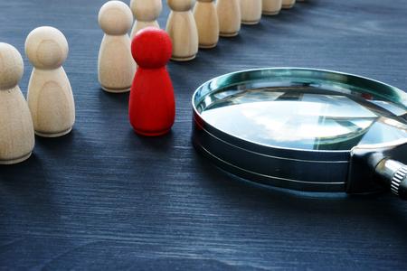 Identificeer begrip. Werving en talentmanagement. Rood beeldje en vergrootglas.