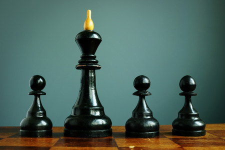 Competitive edge or business advantage in recruitment. Pawns and chess king.