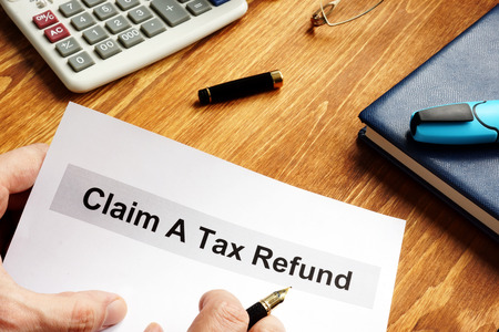 Man is holding Claim a tax refund documents. Stock Photo - 123107266