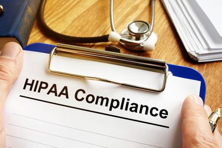 Man is holding HIPAA Compliance application form. Reklamní fotografie