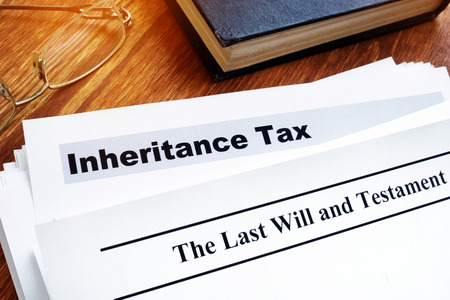Inheritance tax and last will on the desk.