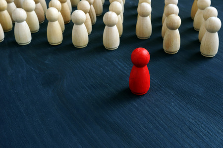 Red figurine in front of line as symbol of leadership. Stand out from the crowd concept.