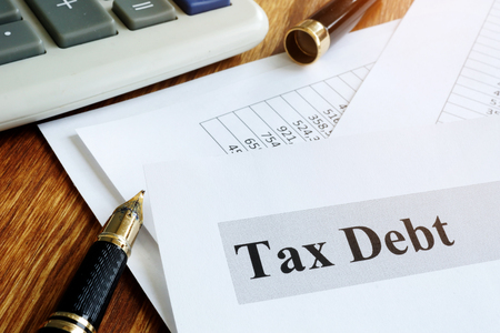 Documents about tax debt on a table.