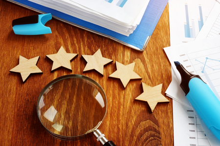 Five stars and magnifying glass. Business appraisal and evaluation. Stock Photo