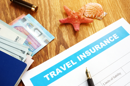 Travel insurance form with passport and cash.