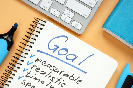 Goal setting concept. Notepad with pen on desk.