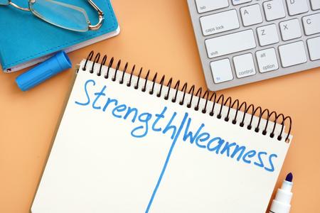 Lista de fortalezas y debilidades en el bloc de notas. Foto de archivo
