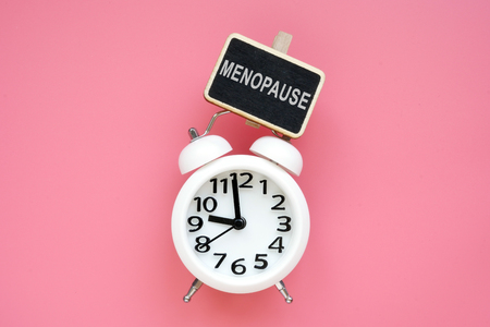 Alarm clock and word menopause on a pink background.