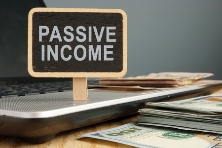 Passive income concept. Notebook and stack of cash.