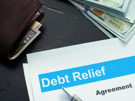 Entschuldungsabkommen und Geldbörse mit Geld.