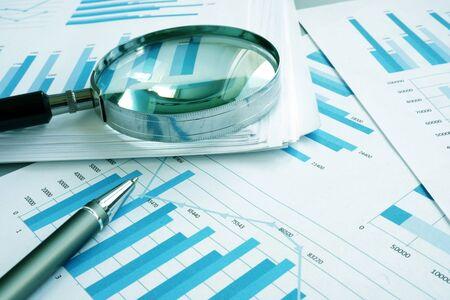 Evaluación y auditoría. Documentos comerciales con gráficos financieros y lupa.