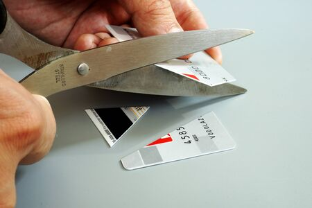 Get out of credit card debt. Man is cutting bank card.
