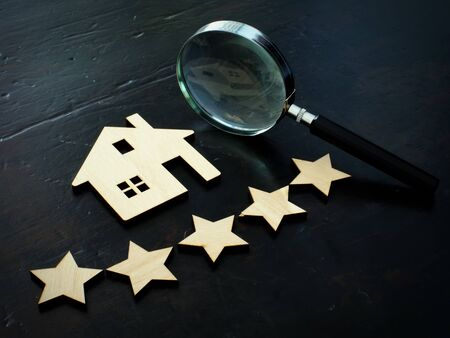 Property valuation and home appraisal. Model of house and five stars.