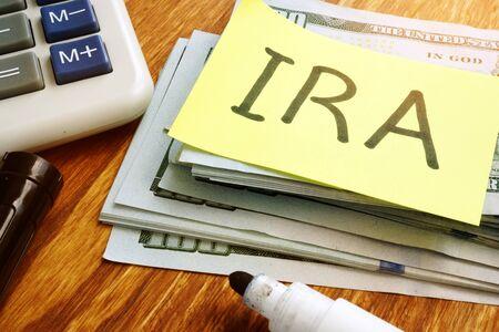 IRA individual retirement account. Stack of money and calculator.