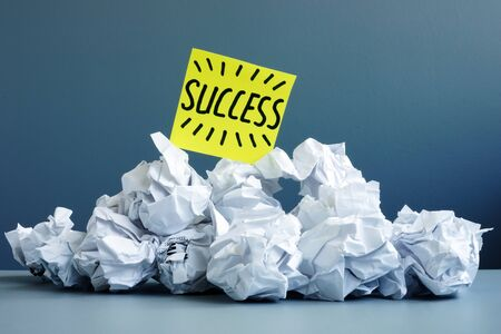 Stack of paper balls as symbol of failure and word success on top.